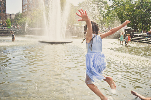 A girl jumping into the water at a city fountain. - gettyimageskorea