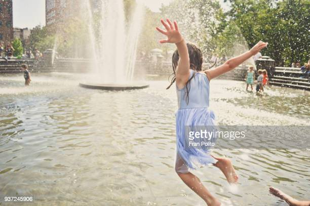 a girl jumping into the water at a city fountain. - spuiten activiteit stockfoto's en -beelden