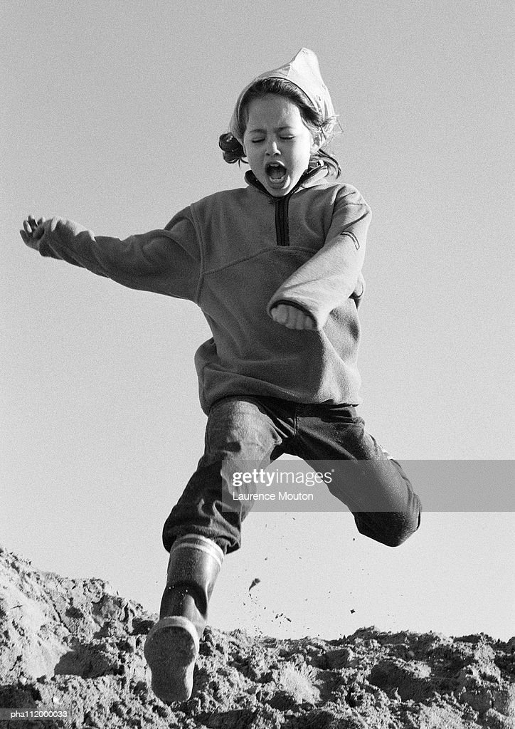 Girl jumping, low angle view, b&w : Stockfoto