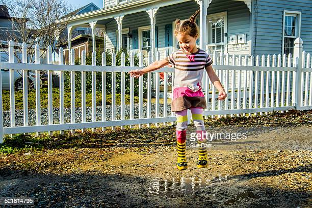 Girl jumping mid air into garden puddle