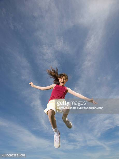 girl (11-12 years) jumping mid air, low angle view, portrait - 12 13 years stock pictures, royalty-free photos & images