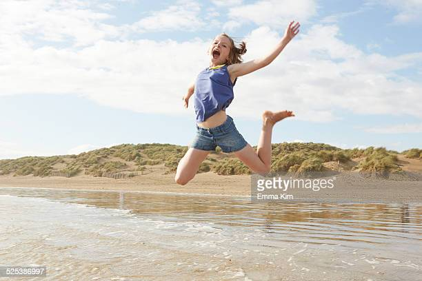 girl jumping mid air on beach, camber sands, kent, uk - camber sands stock photos and pictures