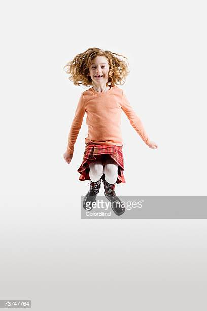 Girl (6-7) jumping mid-air, smiling, portrait