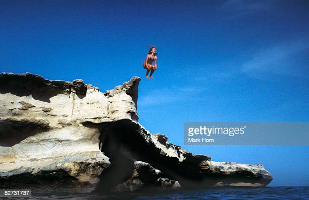 girl jumping of rocks into sea shouting