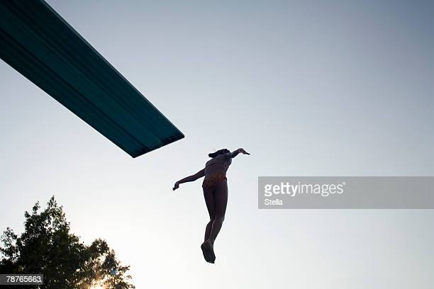 A girl jumping off a diving board