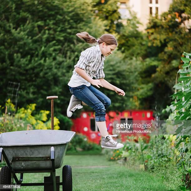 Girl Jumping Off A Wheelbarrow