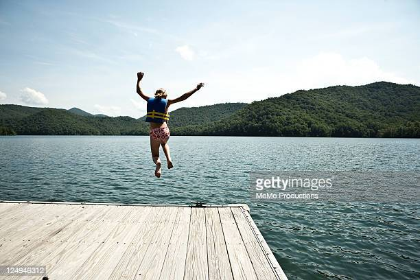 girl jumping off dock. - embarcadero fotografías e imágenes de stock