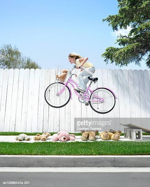 Girl (8-9) jumping off ramp on bike above teddy bears