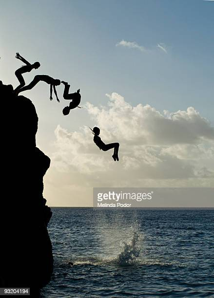 girl jumping off rock at waimea bay - waimea bay stock photos and pictures