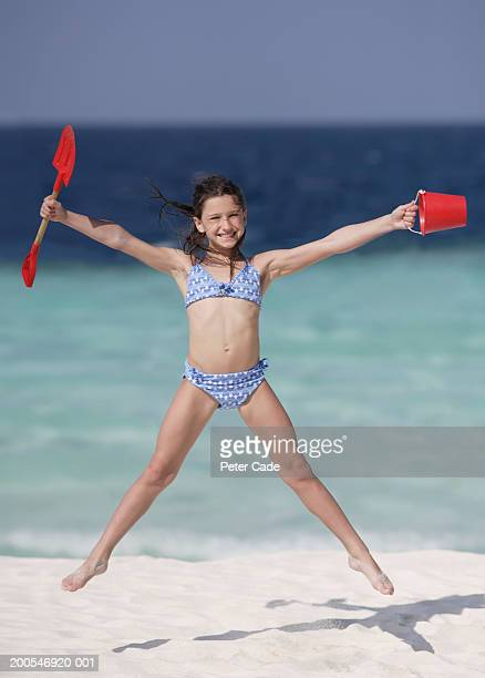 girl (8-9) jumping on beach holding bucket and spade, smiling - legs apart stock pictures, royalty-free photos & images