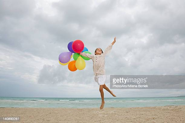 Girl jumping on beach with bunch of colorful balloons