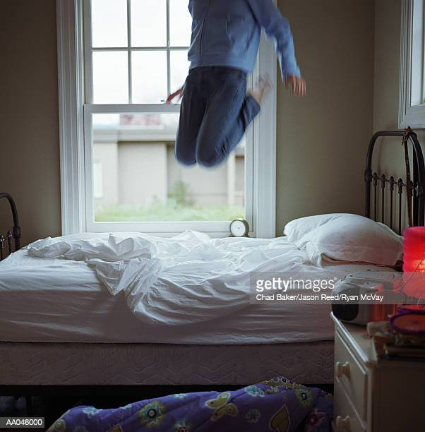 Girl (10-12) jumping on bed, low section (blurred motion)