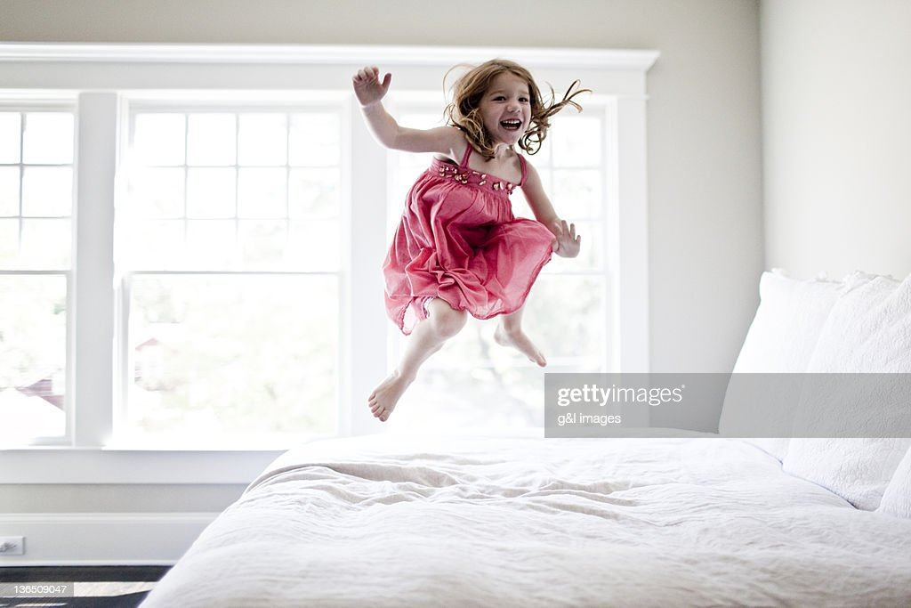 girl jumping on bed : Stock Photo