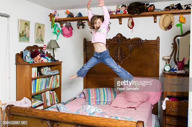 Girl (6-8) jumping on bed