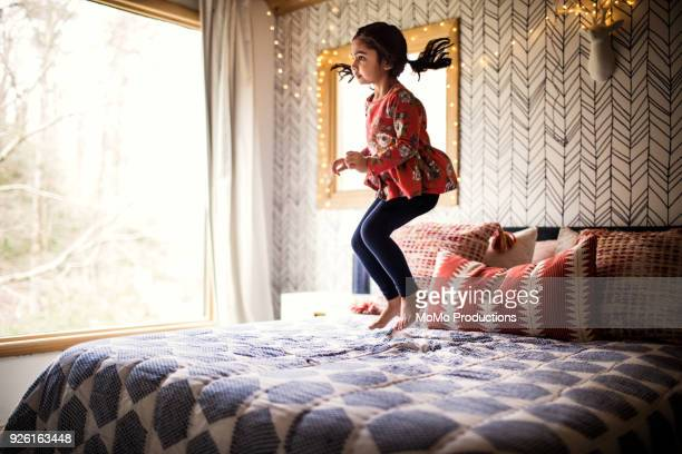 girl jumping on bed - children only stock pictures, royalty-free photos & images