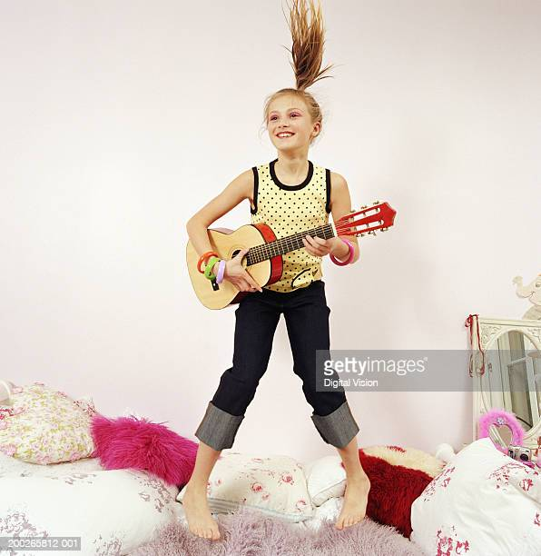 Girl (9-11) jumping on bed, playing with acoustic guitar