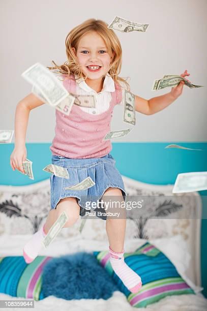 Mädchen springen auf dem Bett mit Dollarnoten