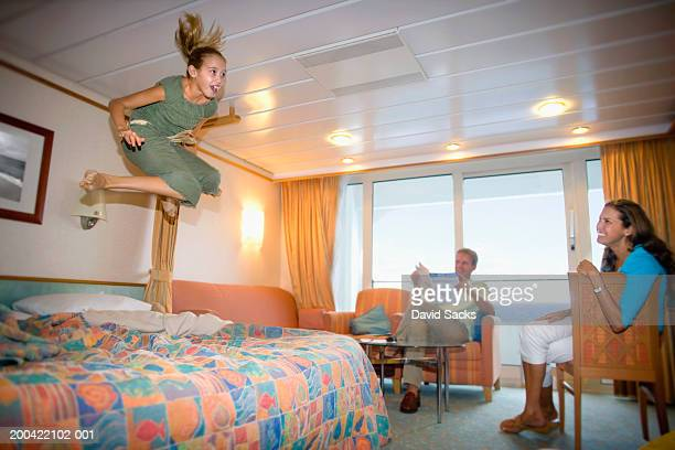 Girl (10-12) jumping on bed with parents in room