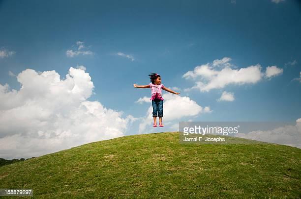 Girl jumping on grassy hill