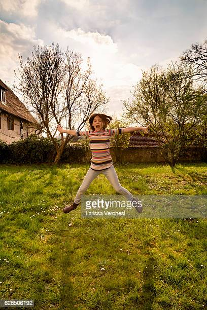 girl jumping on meadow