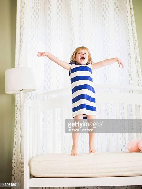 Girl (4-5) jumping on sofa, Los Angeles, California, USA