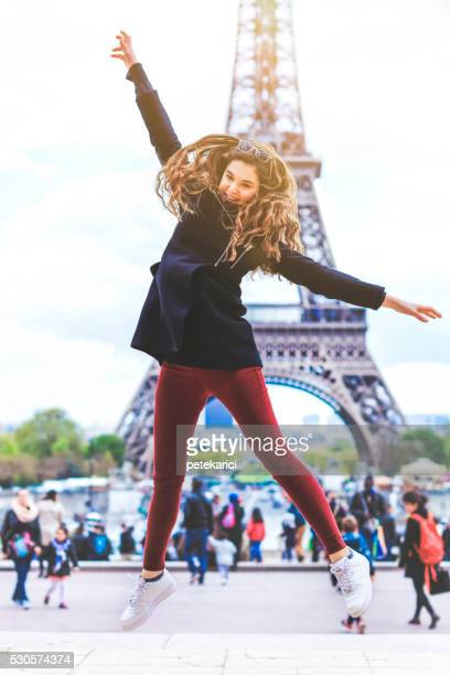Girl jumping on the background of the Eiffel Tower