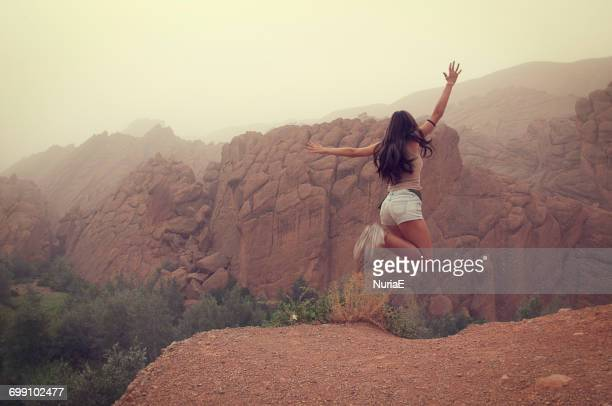girl jumping on the mountain, dades gorges, marrakech, morocco - moroccan girls stock photos and pictures