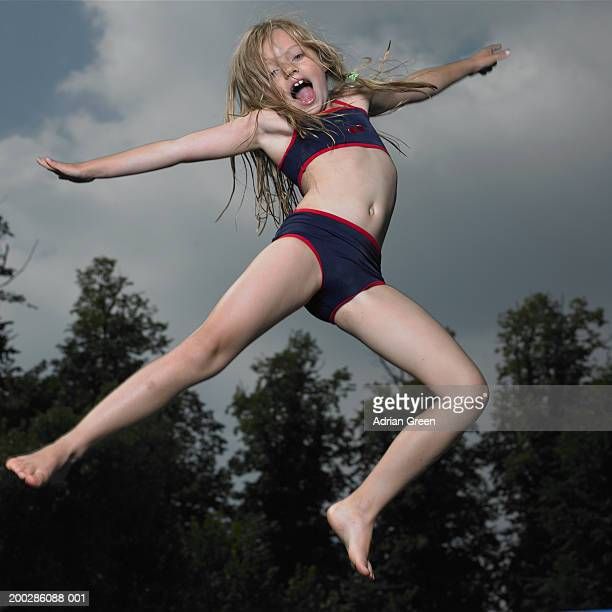 girl (6-8) jumping on trampoline, arms outstretched, portrait - girl with legs spread stock photos and pictures