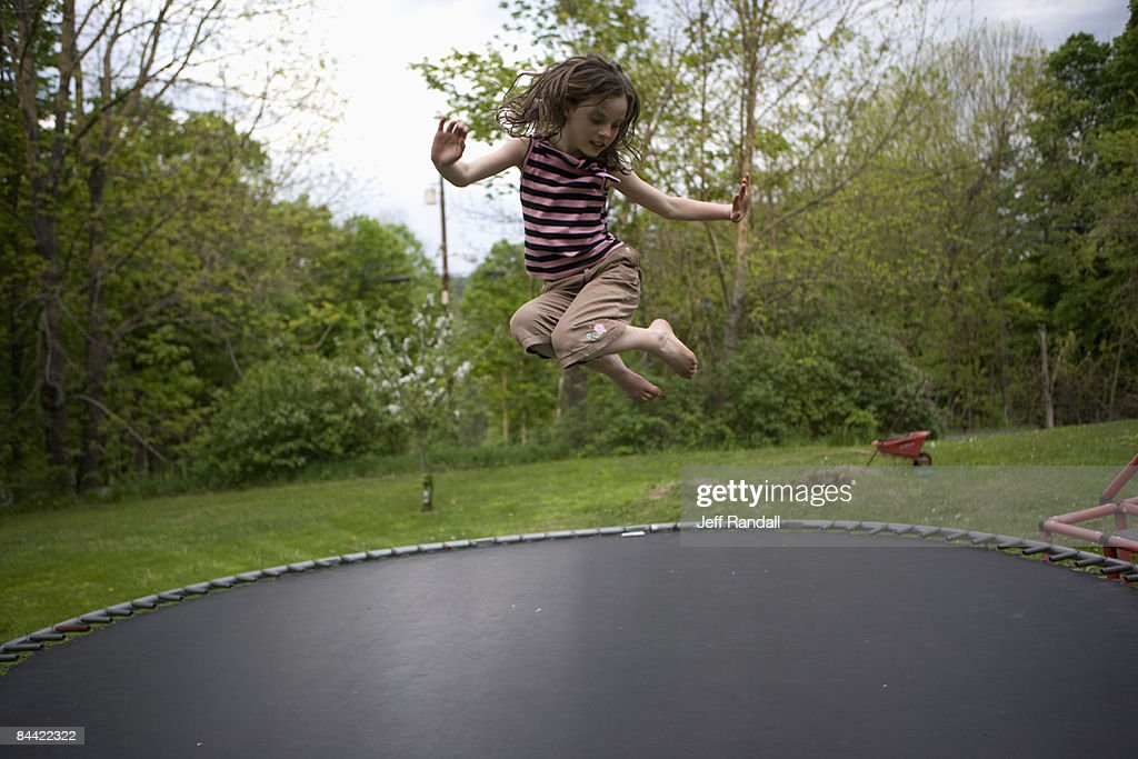 Girl jumping on trampoline : Stock Photo