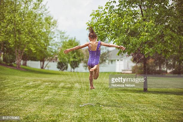 girl jumping over garden sprinkler - rebecca nelson stock pictures, royalty-free photos & images