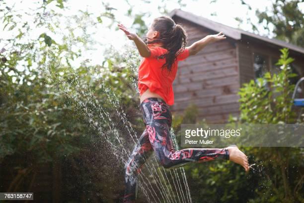 Girl jumping over garden sprinkler