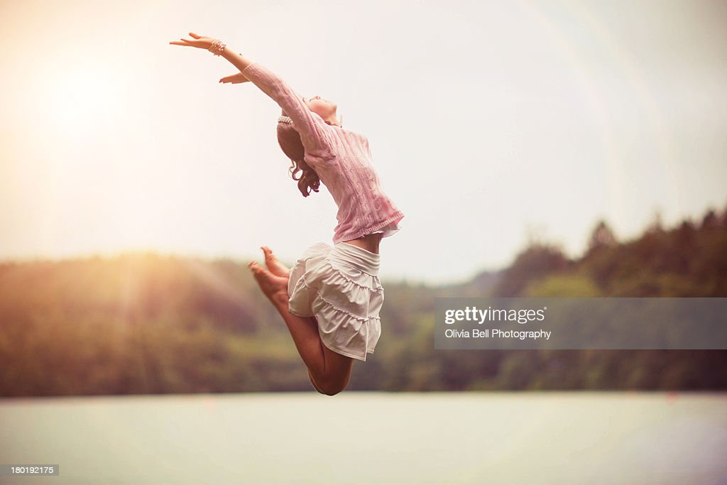 Girl Jumping over Lake : Stock Photo
