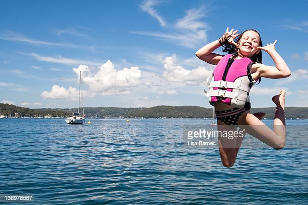 Girl jumping over water