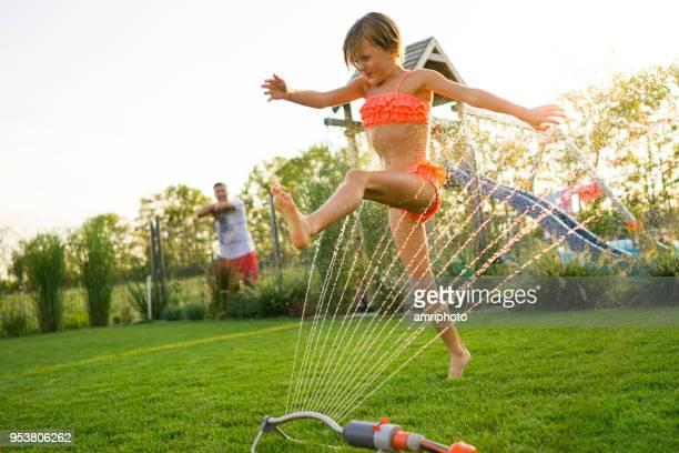 flickan hoppar över vatten sprinkler i trädgården - värmebölja bildbanksfoton och bilder
