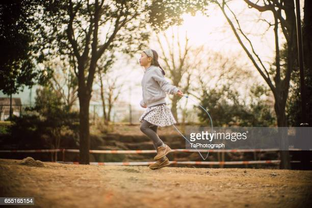 girl jumping rope in park - daily sport girls stock pictures, royalty-free photos & images