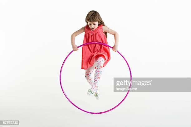 A girl jumping with a plastic hoop