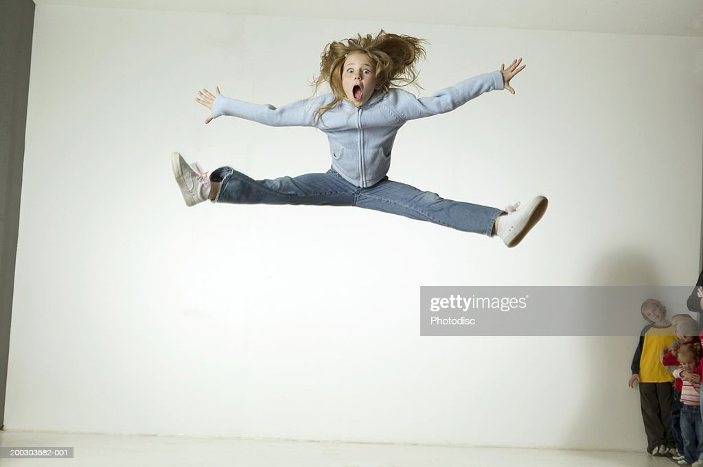 Girl (6-7), jumping with arms and legs outstretched, on trampoline in studio, portrait : Stock Photo