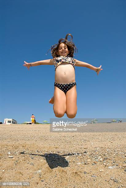 Girl (10-11) jumping with arms outstretched on beach