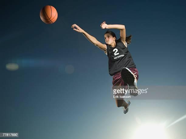 Girl jumping with basketball