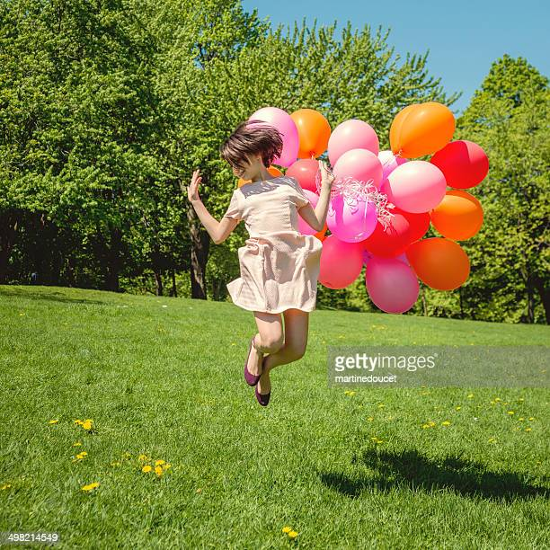 Girl jumping with bouquet of pink balloons in spring nature.