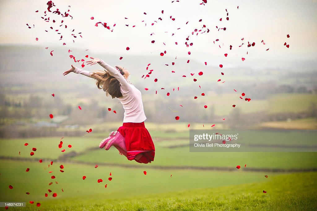 Girl jumping with rose petals in air : Stock Photo