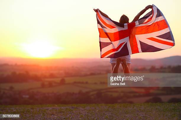 Girl Jumping with Union Jack Flag at Sunset