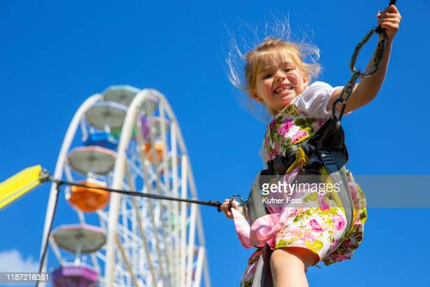 Girl jumps bungee trampoline at a folk festival