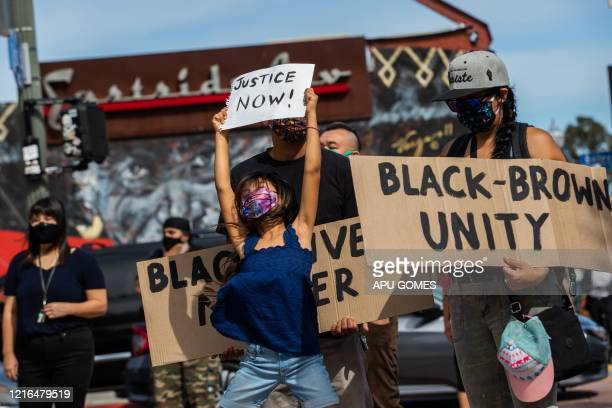 A girl jumps holding a sign while she and her family protest in the Boyle Heights neighborhood of Los Angeles on May 30 2020 in response against the...