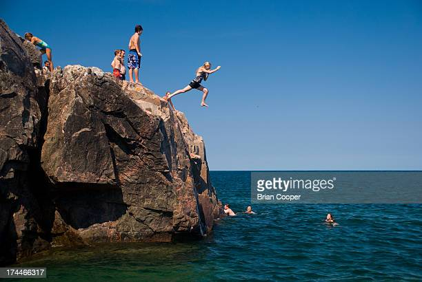 Girl jumps into Lake Superior from the rocky shore of Little Presque Isle in the Upper Peninsula of Michigan.