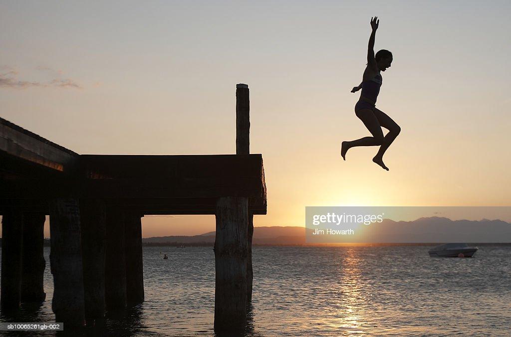 Girl jumps off a jetty into Lake Garda, Peschiera, Italy : Foto stock