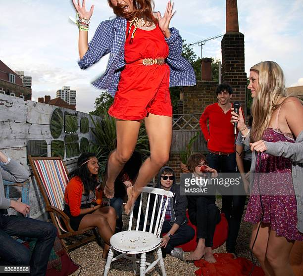 Girl jumps off chair at party