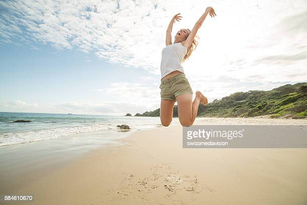 Girl jumps on beach high up in the air