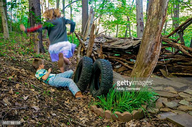 a girl jumps over a boy at their make shift hut in the woods at pittsburgh pa. during the spring - hut stock pictures, royalty-free photos & images