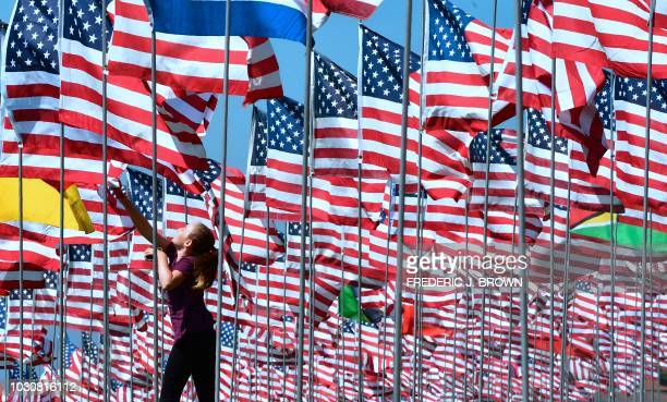 A girl jumps to touch a flag as people visit the 'Waves of Flags' display at Pepperdine University in Malibu California on September 10 where the...
